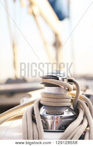 Sailboat detailed parts. Close up on winch and rope of yacht over blue sea. Yachting concept. Shallow depth of field