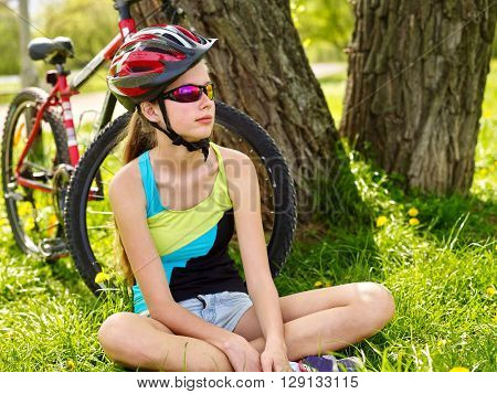 Bikes bycycling girl. Girl rides bicycle. Girl in cycling have a rest sitting under tree. Cycling is good for health. Cyclist looking at looking away and sitting on glass. poster