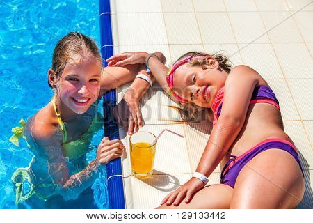 Two children on water slide at aquapark are drinking cold drinks. Children lie on edge of swimming pool. Summer holiday.Outdoor.