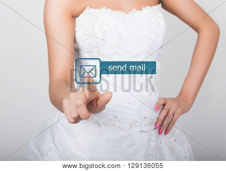 technology, internet and networking concept. Beautiful bride in fashion wedding dress. Bride presses send mail button on virtual screens