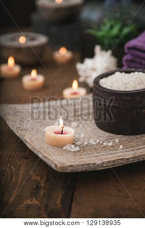 Spa and wellness setting with natural bath salt candles towels and flower. Wooden dayspa nature set