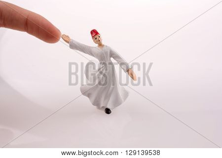 Hand holding a Sufi Derviş on a white background