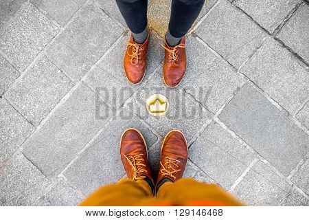 Couple standing near the small crown symbol on the sidewalk in Bratislava city in Slovakia