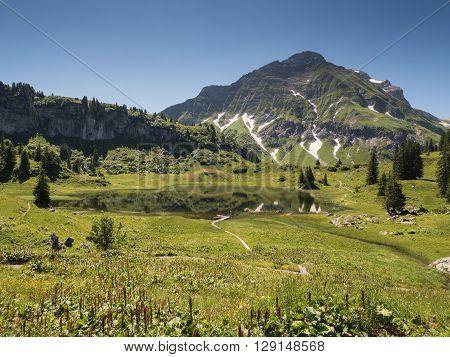 A view of Alpine mountains and the Koerbersee lake near the village Schroecken in Bregenzerwald region Vorarlberg Austria