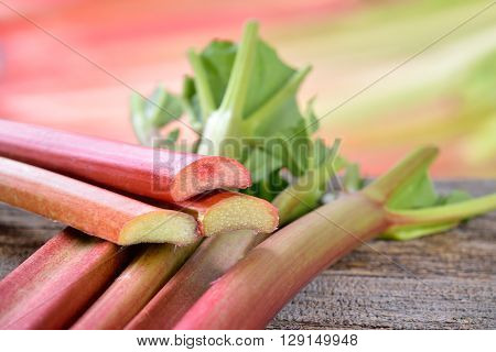 Fresh unpeeled rhubarb on a wooden table, in the background other rhubarb stalks in soft focus
