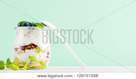 Yogurt oat granola with jam, blueberries and green leaves in glass jar on pastel mint backdrop, copy space