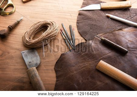 Leather craft. Leathersmith's work desk . Pieces of hide and leather working tools on a work table.