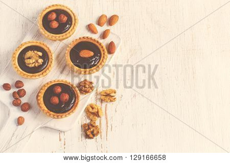 Almond walnut hazelnut chocolate small tarts on a white background space for text vintage toning