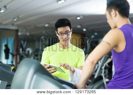 young asian people talking by tablet in modern gym