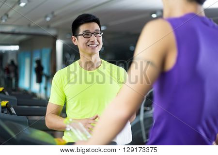 young asian people talking in modern gym