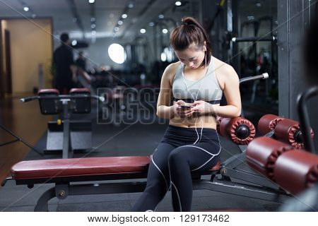 young asian girl with smart phone in modern gym