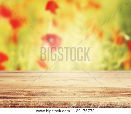 Old wooden board against poppy field