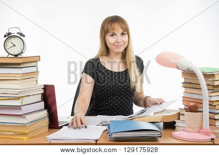 Girl With A Smile Sitting At His Desk Littered With Books