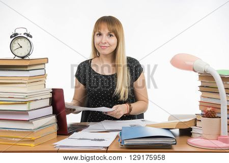 The Girl Behind The Desk Littered With Books With A Smile, Holding A Paper