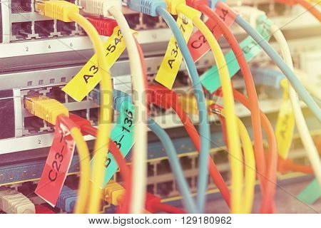 Telecommunication ethernet cables connected to Internet switch. Data center concept