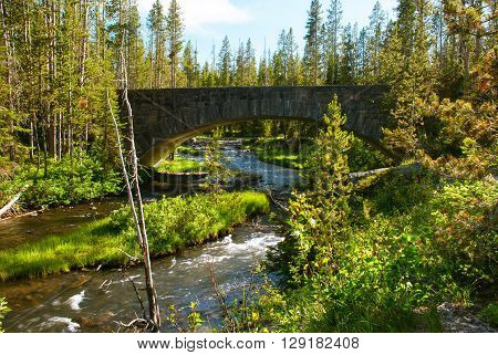 A beautiful arched bridge over the Lewis River near the Moose Falls Yellowstone National Park