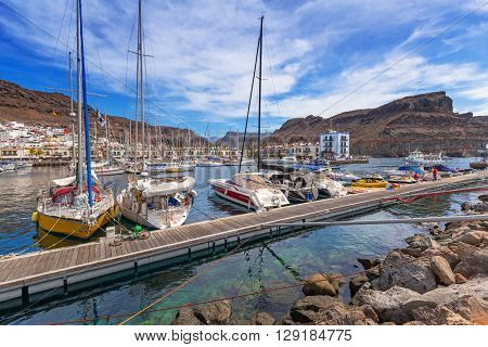 PUERTO DE MOGAN, GRAN CANARIA, SPAIN - APRIL 21, 2016: Yachts in the harbor of Puerto de Mogan, a small fishing port on Gran Canaria, Spain. Puerto de Mogan is called a Little Venice of the Canaries.
