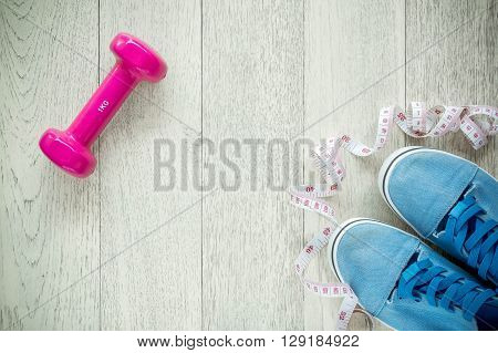 Fitness background with dumbbells and sneakers on wooden. View from above.