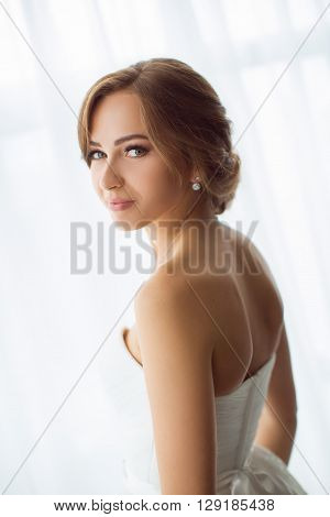 Beautiful young bride portrait in white wedding dress indoors.  Luxuty model standing against big window at home. Girl waiting her groom and looking at camera in bright room. Beautiful wedding hairdress and make-up. High key photo.