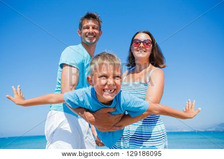 Happy cute boy with his mother and father having fun on beautiful sunny beach