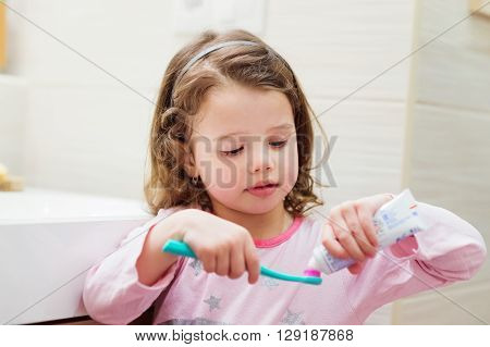 Cute little girl in her pyjamas in bathroom putting a toothpaste on toothbrush