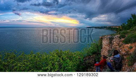 young couple watching the sunset on a high cliff - panoramic view copy space