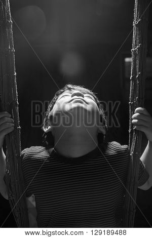 Little boy playing swing indoor rim light black and white