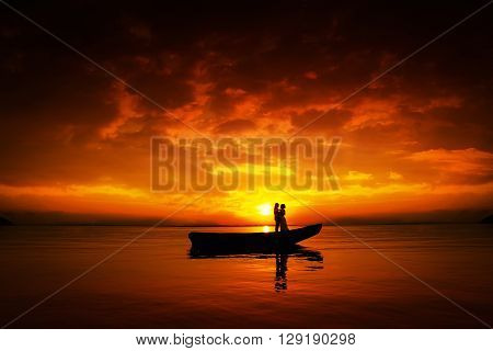 Silhouette of a couple in love. Young people in boat on river in sunset beautiful skyes.