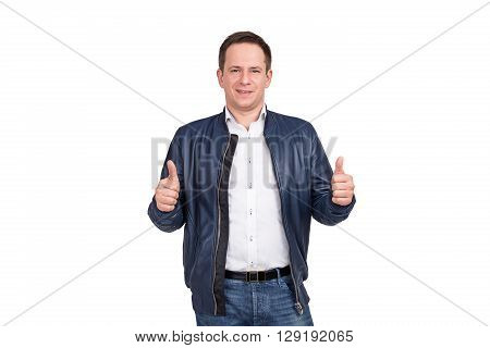 Handsome European Man In White Shirt, Blue Jeans And Blue Leather Jacket Holds His Thumbs Up. Isolat