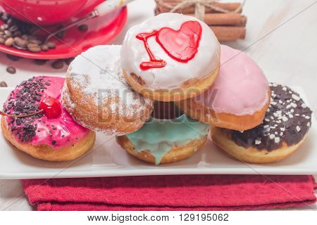 Donuts on a plate and coffee on white wooden background.