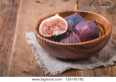 Group of fresh figs in a bowl and on rustic wooden table