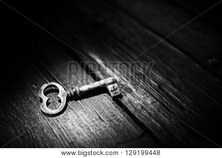 Rusty key on old wooden surface, black and white photo.