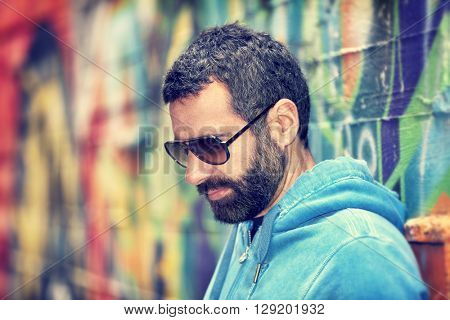Closeup portrait of handsome man with stylish beard and sunglasses, standing over colorful city wall background, fashion street look, urban lifestyle