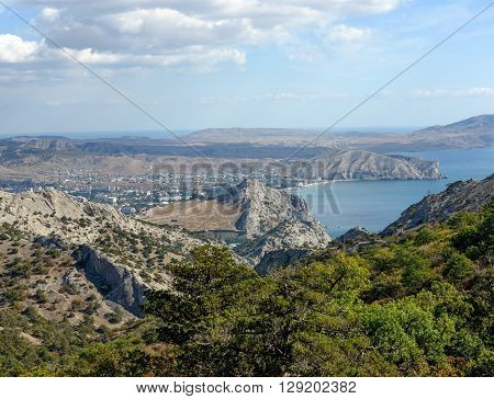 Scenic high angle view towards Sudak town valley behind Genoese Fortress Alchak Cape and valley between it and Meganom Cape is from north face of Sokol (Hawk) Mountain near New World (Novyi Svet) town in Crimea Russia.
