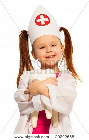 Smiling girl with pigtails dressed as a dentist hugging big tooth dummy, isolated on white