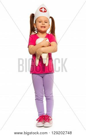 Little girl in doctors cap holding big tooth model, isolated on white