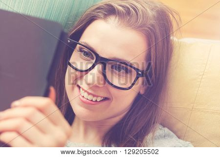 Happy Young Woman Reading An E-book On Her Couch
