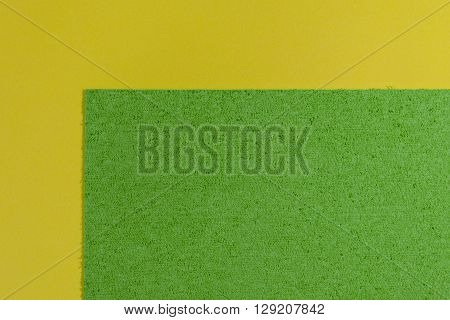 Eva foam ethylene vinyl acetate sponge plush apple green surface on lemon yellow smooth background