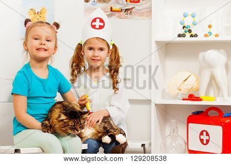 Little girls playing veterinarian with a cat, getting a vaccine, isolated on white background