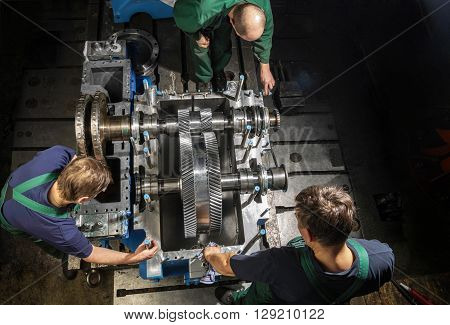 Working people with a small steam turbine. Metal gears. Gear wheels of the engine.