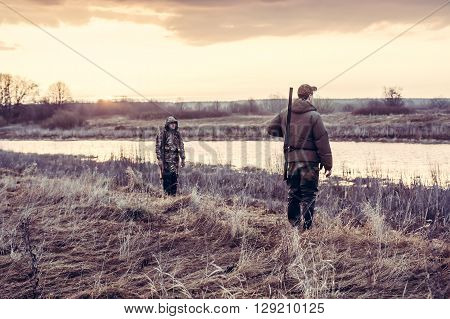 Hunters choosing a good position  for duck hunting in field nearby river during sunrise