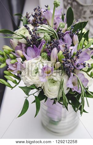Modern bride bouquet of violet freesia, white buttercup ranunculus peonies, green leaf, lilac lavender, roses, rosemary in bunch flowers. Rustic style wedding nosegay. Spring summer holiday wedding floral arrangement on white background.