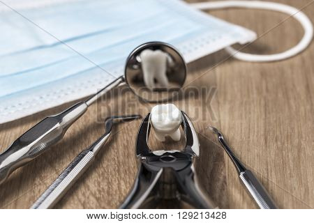 Tooth extraction concept with an array of stainless steel dental tools and a mask with the extracted tooth clasped in the pincers and reflected in the mirror
