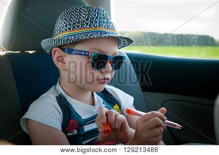 The child draws while traveling in the car