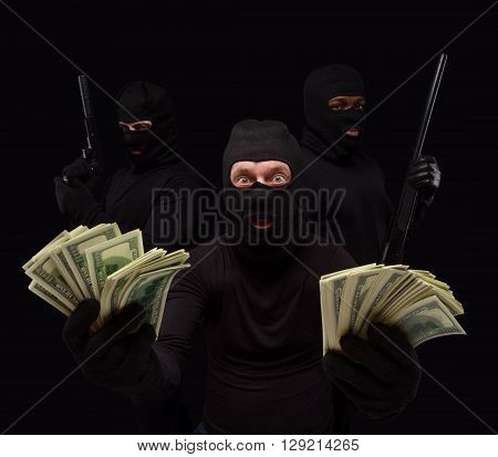 Portrait of gangster showing money stolen from house, apartment, flat, etc. Thieves in masks over black background. Isolated on black.