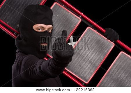 Masked thief showing middle finger in studio while carrying ladder for robbery or burglary. Mafia concept. Studio shot. Isolated on black.