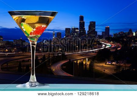 Martini glass with two dibs inside against the view of city skyline