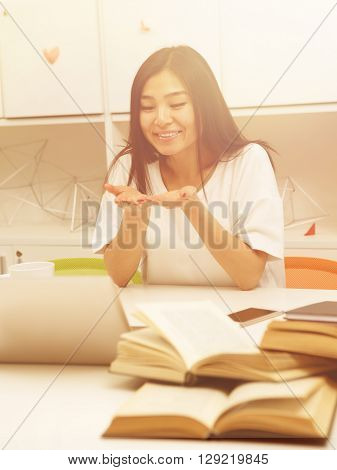 Toned image. Asian student studying in library and doing air-kissing while communicating with foreign friends via Skype o laptop computer.
