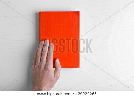 Male hand hold the red  book on white table.
