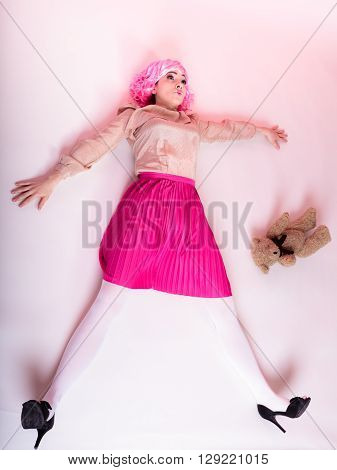 Mental disorder concept. Young childlike woman wearing like puppet doll holding teddy bear toy studio shot